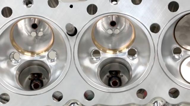 画像: TF用エンジンの燃焼室。点火には14mmのツインプラグ方式を採用しています。各インレットポートに見える2つの穴は、インジェクター用です(計16本)。 www.youtube.com