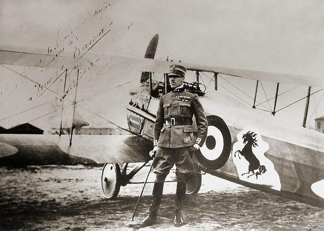 画像: 第一次世界大戦でイタリアのエースパイロットとして活躍したフランチェスコ・バラッカ。愛機スパッドの機体には、「跳ね馬」が描かれています。なおバラッカは、この写真が撮影された1918年に亡くなっています。 en.wikipedia.org