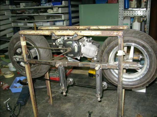 画像: 鉄の角材でやぐらを作って、そこにポケバイのホイールとエンジン、そしてチェーンが組み込まれます。この2つのタイヤに、バンドソーがセットされるワケですね。 www.youtube.com