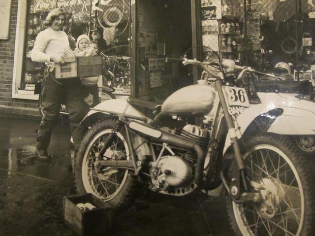 画像: 経営するモーターサイクルショップの前で、赤ちゃんを箱に入れて運ぶレネー。母は偉大です! www.reneebennett.co.uk