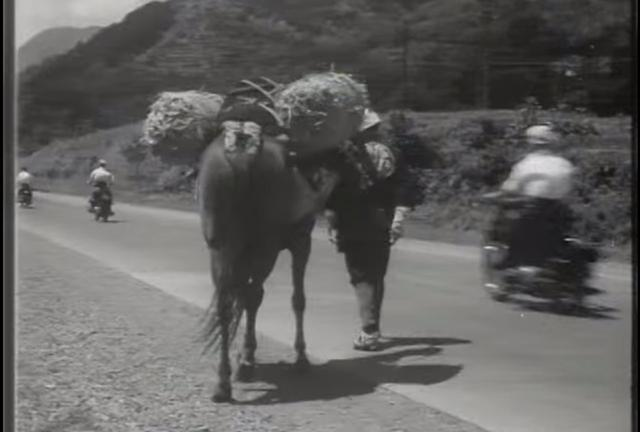 画像: 1950年代、荷馬のうしろを駆け抜けていくメグロのバイク。