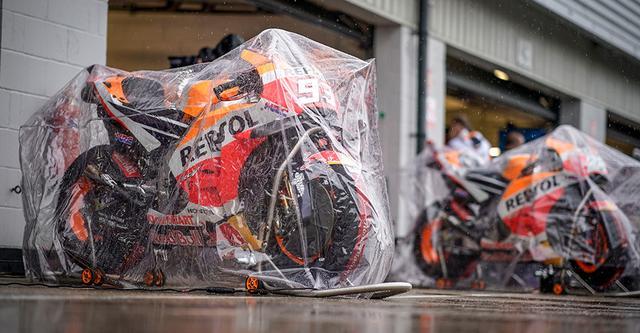 画像: レプソル・ホンダのピット前。雨に濡れないように、ホンダRC213Vにカバーがかけられています・・・。 www.honda.co.jp