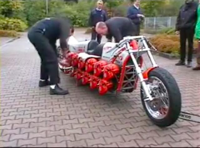 画像: 2人の男の人が、リコイルスターターを引っ張ってエンジンを始動させます。ひとつひとつやるので、なかなか面倒くさそうです(笑)。 www.youtube.com