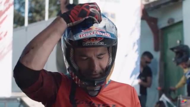 画像: レッドブル主催のアーバンMTBダウンヒル大会に出場するトマス・スラヴィク。ヘルメット頂部を触り、ある異変? に気づきます・・・。 www.youtube.com