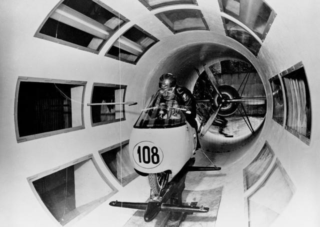 画像: 前輪を覆うダストビンフェアリングを装着したモトグッツィレーサーの風洞実験の様子。軍用のフィアットV型12気筒(約900馬力)のエンジンで、風を風洞内に発生させる仕組みです(後年にはエンジンから、電気モーターにアップデートされました)。 www.motoguzzi.com