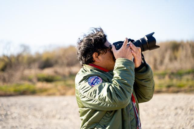 画像: カメラを構えると自分だけの世界に入り込む河合さん。どんなときもカメラは手放せない。
