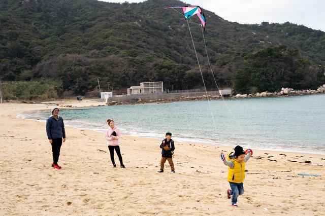 画像: 海辺で凧揚げを楽しむ浦山さん一家。休日はこうして自然の中で遊ぶことが多いそうだ。