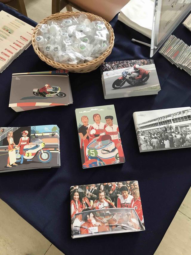 """画像: こちらの6種類のポストカードはなんと無料配布! そしてヤマハコミュニケーションプラザ特製の""""ラムネ""""(後方のカゴの中)も、ぜひご賞味ください。各種ヤマハ製品が描かれていて、とても可愛いお菓子です。"""