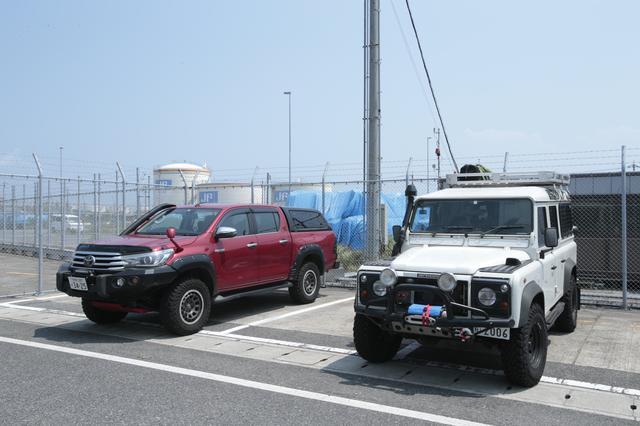 画像: 左が谷さんのトヨタハイラックス、右が江頭さんのランドローバー・ディフェンダー。ちなみに谷さんはオートマ派、江頭さんはマニュアル派です! ©︎奥村純一