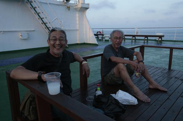 画像: 谷さん(左)と江頭さん。心地良い風に吹かれながら、フェリー船上で酒盛りをエンジョイ。四駆好きのお2人は、国内を走り尽くした! ということで、ロシアやモンゴルやオーストラリアなど、さまざまな国にアドベンチャーライドを満喫するようになったとか。こんな風に趣味に全力投入するオジサマたちって、素敵ですよね! ©︎奥村純一