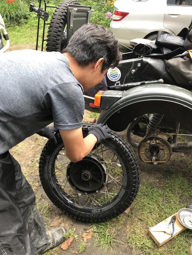 画像: 側車側のドラムブレーキの点検をする堀田さん。なお氏のウラルは、2013年型のキャブレター(ケーヒンCVK)モデルです。