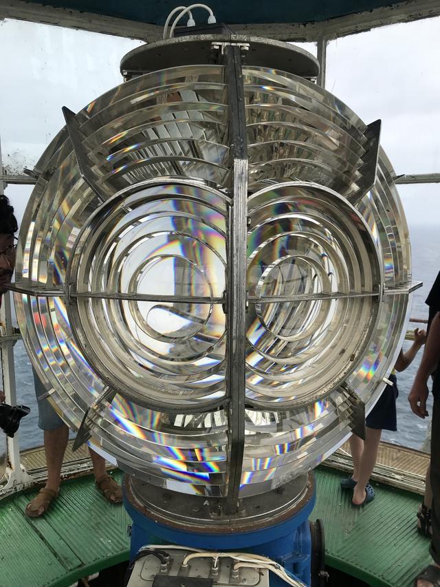 画像: 複雑な構造の巨大なレンズが登場します! フィリップスと共同開発した特殊なレンズで、60km先からその灯りを見ることができるとのこと。現在は25年周期で交換する電球バルブが光源ですが、建造初期のころは燃料を燃やすランプがその役目を果たしていました。