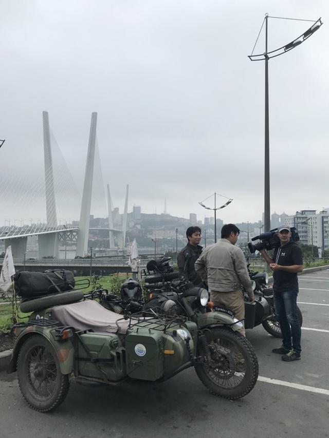画像: 2012年、APEC開催時に合わせ開通した「金角湾大橋」をバックに、メディア取材を受ける堀田さん(左)と堀内さん。