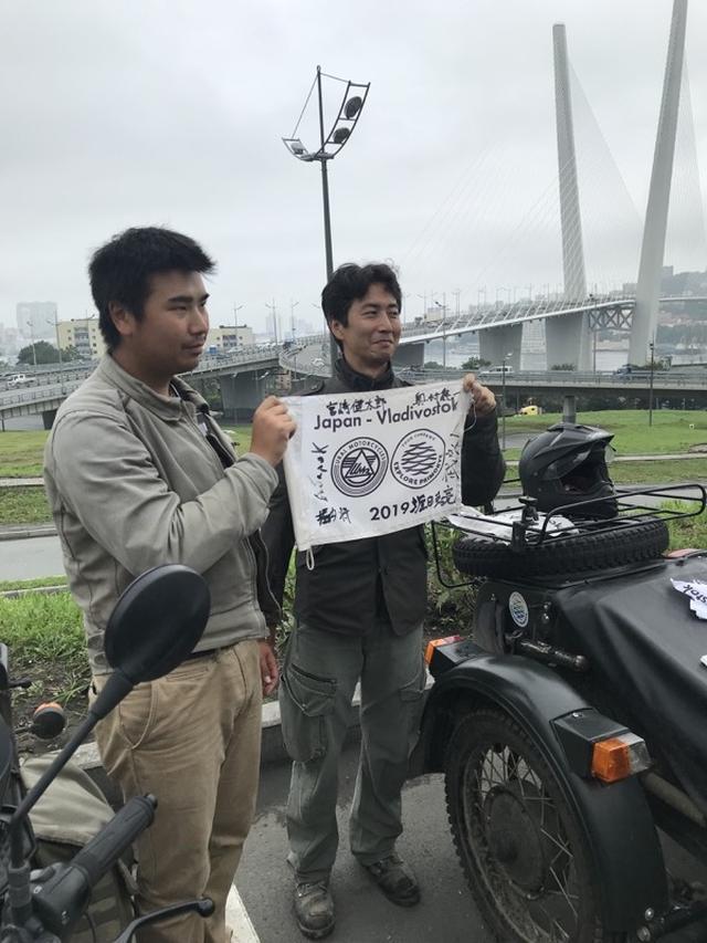 画像: ウラル・ロシア・ライド2019の旗に、寄せ書きサインをしたものを掲げる堀内さん(左)と堀田さん。地元メディア取材も2度目となると、緊張感もなく余裕すら漂わせています!?