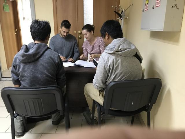 画像: 事務所内にて、業者のお姉さんの指示に従い書類にサインする3人。朝食抜きでロシアメディア取材対応と、通関手続きをするという、慌ただしいこの日の午前でした・・・。