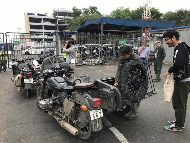 画像: それぞれのウラルを預ける前に、ヘルメットなどのライディングギアを側車のシートやトランクなどに収納。奥村カメラマン(右)はちゃっかり、自分の重い荷物をこのあと自分の手で持ち運ぶことを厭って、堀田さんに荷物を預けています・・・ワガママな人には困ったモノですね(苦笑)。