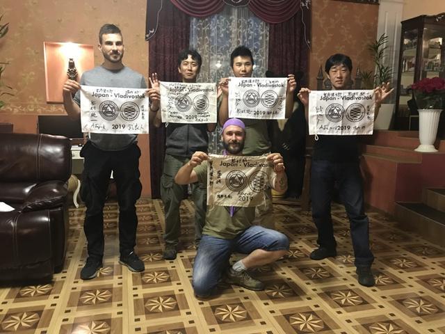 画像: ウラル・ロシア・ライド最後の夜となった8月13日、ホテルのロビーで寄せ書きをしたツアー旗をそれぞれ手にして記念撮影! 左からブラドさん、堀田さん、堀内さん、私(宮﨑)、そして手前のセルゲイさん。