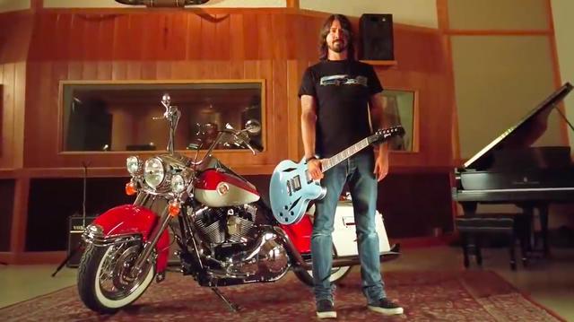 画像: デイヴの愛車、ロードキングとともに。フー・ファイターではフロントマンのデイヴはボーカルとギターがメインですが、動画の中では彼の「ドラム」を堪能することができます。 www.youtube.com