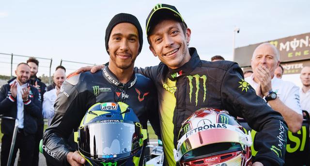 画像: 互いのヘルメットを持って、肩を組むL.ハミルトン(左)とV.ロッシ。 www.yamahamotogp.com