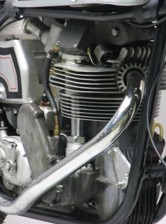画像: 1956年型ノートンマンクス40M(350cc)機関部。このエンジンはボア・ストロークや動弁系の変更などを受けて長年発展しましたが、OHC単気筒というフォーマットは変わることはありませんでした。 upload.wikimedia.org