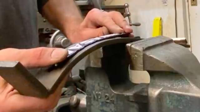 画像: まっすぐな状態で供給される燃料タンクエンブレムを、燃料タンク側面に沿うように曲げるための「ガイド」となる板を作っていたわけですね・・・。 www.youtube.com