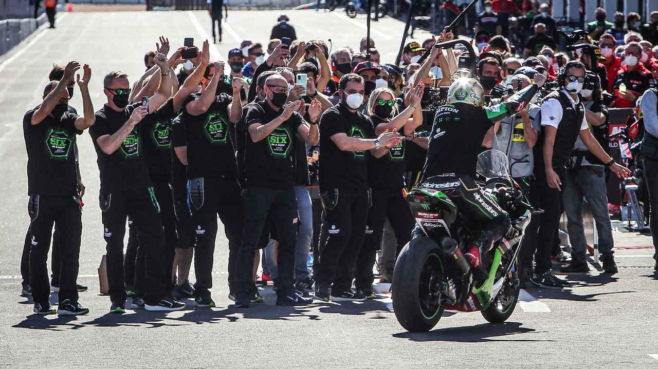 画像: 毎年恒例となった、チャンピオン獲得記念の「金」のヘルメットを被り、6連覇記念Tシャツを身に纏ったスタッフたちから祝福を受けるJ.レイ(カワサキ)。彼のSBKにおける「王朝」は、いつまで続くのでしょうか? www.worldsbk.com