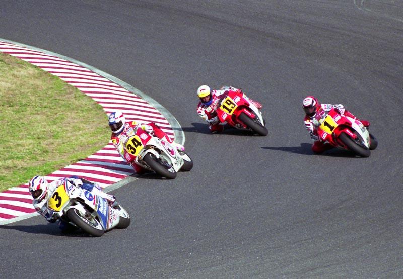 画像: 1991年の日本GP500ccクラス。先頭からミック・ドゥーハン(ホンダ)、ケビン・シュワンツ(スズキ)、ウェイン・レイニー(ヤマハ)、ジョン・コシンスキー(ヤマハ)。当時の最高峰クラスは、黄色字に黒数字が指定されていました。 en.wikipedia.org