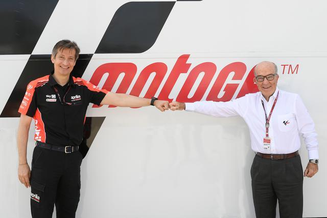 画像: 距離を保ち、グータッチをするアプリリア・レーシングCEOのマッシモ・リヴォラ(左)と、ドルナ・スポーツCEOのカルメロ・エスペレータ。