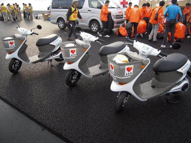 画像: 2011年11月20日、「東日本復興支援ふじのくに新東名マラソン」に大会サポート車両として貸与されたe-Let'sの実証実験車。貸与された合計9台の内訳は、移動審判車3台、救護車を兼務するAED積載車3台(写真)、大会連絡車3台でした。 www.autoby.jp