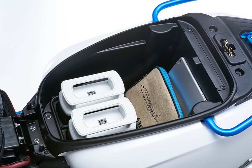 画像: 収納スペースの前寄りに積まれるのが、アイオネックス交換式バッテリーです。 www.kymco.com