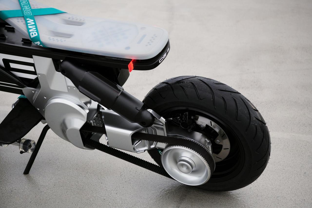 画像: スイングアームは片持ち式で、1本のショックユニットがレイダウンレイアウトで組み合わされています。後輪の駆動にはチェーンより静粛性に優れるコグドベルトが使われており、オイリーさを排除できるEVの特性をさらに活かしています。シート前側でクロスしているラバーバンドは、小物を挟んで固定できたりします。 www.bmw-motorrad.com