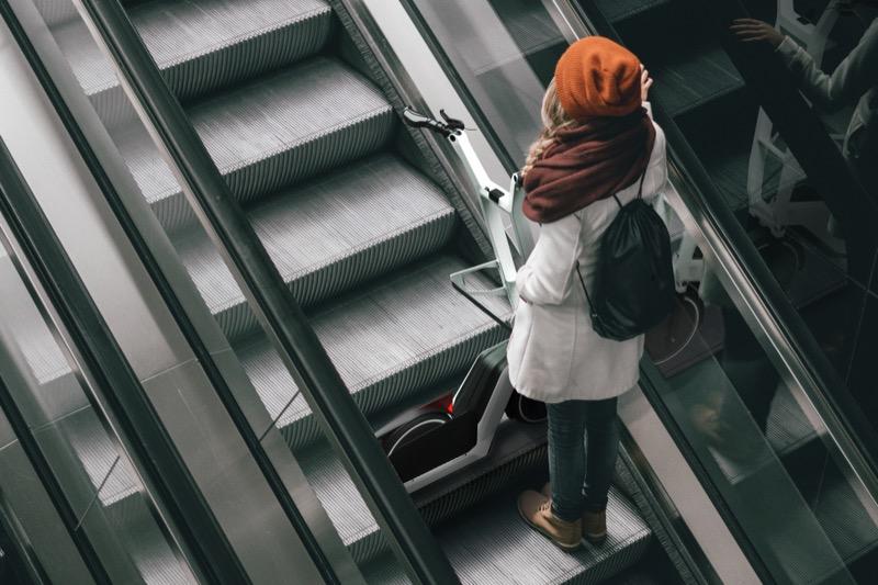 画像: SoFlow コンセプト クレバー コミュート インスパイアド バイ BMWを、「公共交通機関モード」にした状態。前後長が大幅に短縮されるので、このとおりエスカレーターに載ることも可能です。乗車して移動することが禁じられている地下道を利用する場合などにも、ありがたい機能と言えるでしょう。 www.bmwgroup.com
