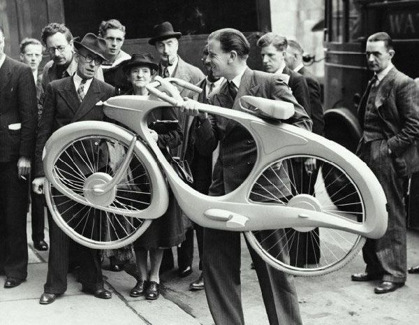 画像: 1946年、「未来の自転車」を持ち上げるB.ボウデン。1930年代アメリカで流行した「流線形」のスタイリングが多くの人の目をひきましたが、そのメカニズムにも注目すべき点がふんだんにありました。なおボウデン自身は、自作に「ザ・クラシック」という名を与えています。 www.nostalgic.net