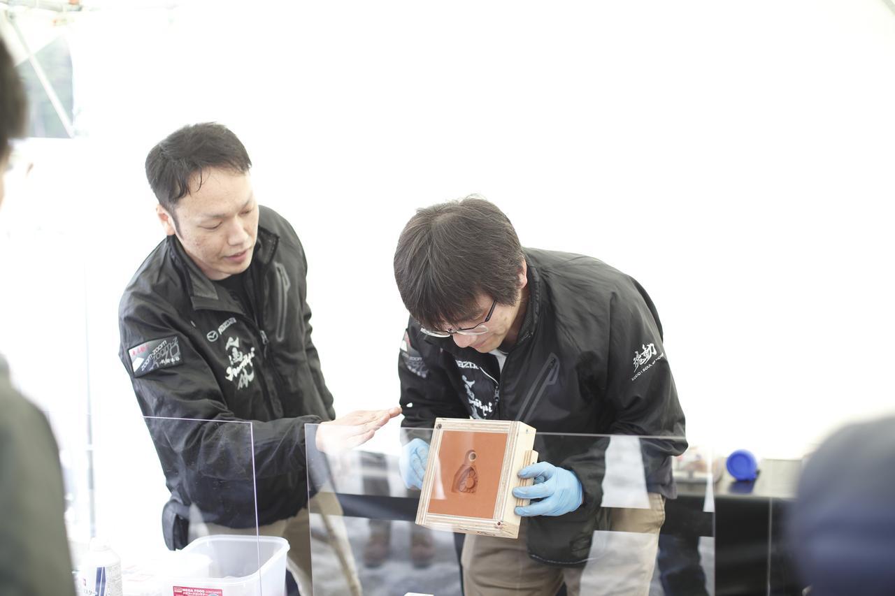 画像: 砂型鋳造の説明をするマツダのスタッフ