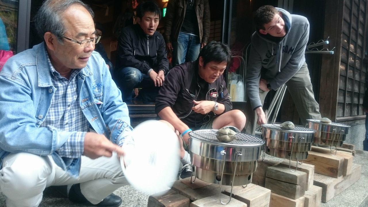 画像: ミーティング名物『焼き蛤グランプリ』。うちわで七輪の上の蛤をあおぎ、早く開かせた人が勝ち。 今年で20回目の開催で、貴島さんも参加。