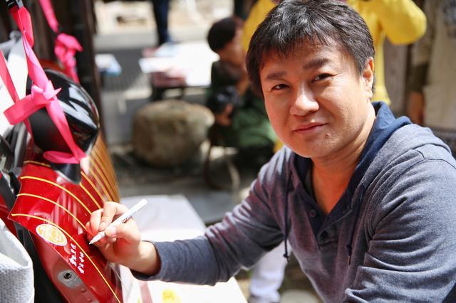 画像: イベント代表の倉元さん。サインカーのパーツに一番最初にサインをします。