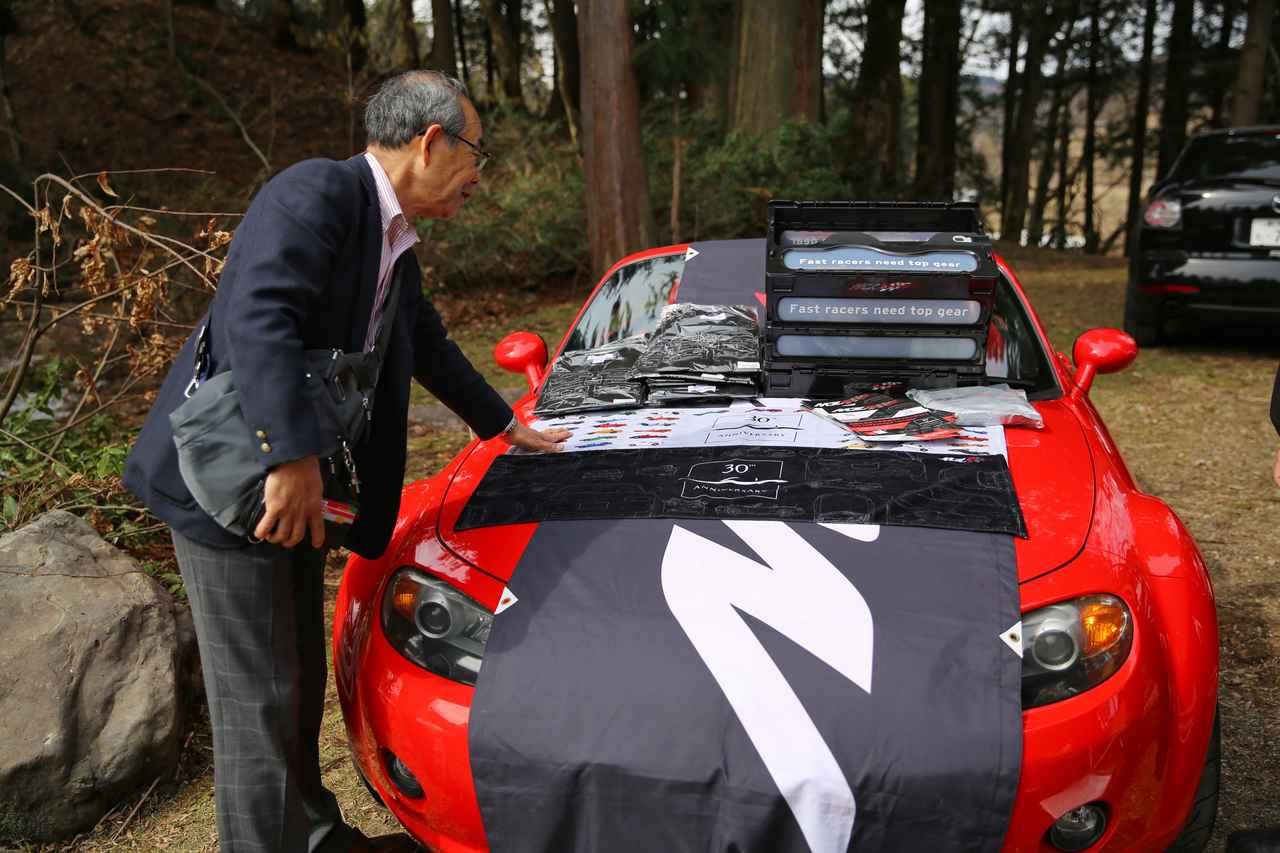 画像: ロードスター開発の第一人者、貴島孝雄さんもMZRacingのロードスターグッズに興味津々。