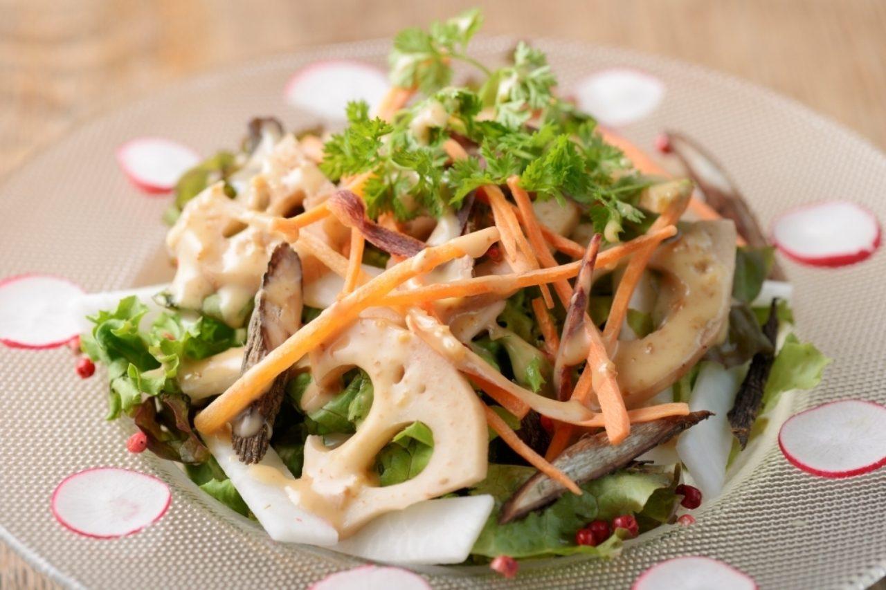 画像: ◎噛んで楽しい!『5種の根菜サラダ』(税抜き価格:レギュラー930円、ハーフ650円) ごぼう、れんこん、ラディッシュなど、5種類の根菜をメインに、風味豊かな胡麻ドレッシングで仕上げました。咀嚼回数が増えるよう、根菜を少し大きめにカットしました。また、抗酸化作用のあるナッツ類も添えています。