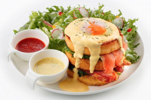 画像: タワーエッグベネディクト Tower Eggs Benedict (全店共通) レギュラー1,900円 驚きのエッグベネディクト登場です!!!3段に重ね上げたフレンチトーストの間に、ホエー豚の熟成ベーコン、スモークサーモントラウト、ホウレン草をサンドし、オランデーズソースをかけました。 横に添えたバジルオランデーズソースとトマトソースで、また違った味をお楽しみください。