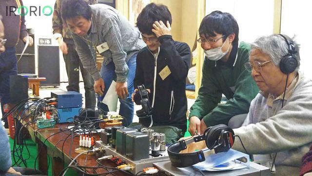 画像1: 2016年12月29日、夕日が差す東京都世田谷区の閑静な住宅街。 年越しを控えた街で「初詣」の赤いのぼりを掲げた寺に、男性たちが20人以上も続々と集まってきた。 親しげに会話を交わす彼らの手は、大事そうに機械を抱えている。 これが、この寺で20年余り続くディープすぎる趣味人の集い「お寺大会」の幕開けである。 ちなみに、この妙法寺は「回る大仏」として知られる「おおくら大佛」が鎮座するお寺だ。 いったい、何が始まるのか!? 箱の中は「手づくりアンプ」 彼らの正体は、アンプづくりを趣味とする「手作りアンプの会」のメンバーである。 1995年に、自作オーディオから音を出す喜びを伝えようと設立。 メンバーは音楽好きが高じて、オーディオ機材を自 [...] irorio.jp
