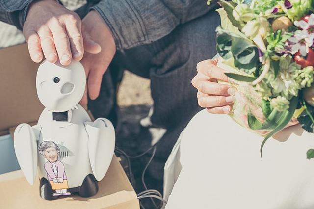 画像1: 結婚式に「分身ロボット」で参加できるサービスが始まった。 「分身ロボットOriHime」で結婚式に参加 「結婚式に招待されたけど遠すぎて行けない、体の調子が悪くて行けない...」と泣く泣く参列を諦めたことがある、という人もいるのではないだろうか? そんな悩みを解決してくれるサービスが登場した。 オリィ研究所は先日、分身ロボット「OriHime」で結婚式への参加を可能にする「OriHimeブライダルサービス」をスタート。 OriHimeがあなたの分身となって、結婚式に参加する。 ネットで遠隔操作、拍手や挨拶も 分身ロボットOriHimeは、カメラやマイク、スピーカーを内蔵しており、「操作する人の分身」に。 操作者はiPadやパソコンなどを [...] irorio.jp