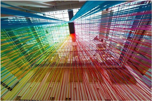 画像: カラーテープでつくられた巨大な虹のようなインスタレーションが幻想的