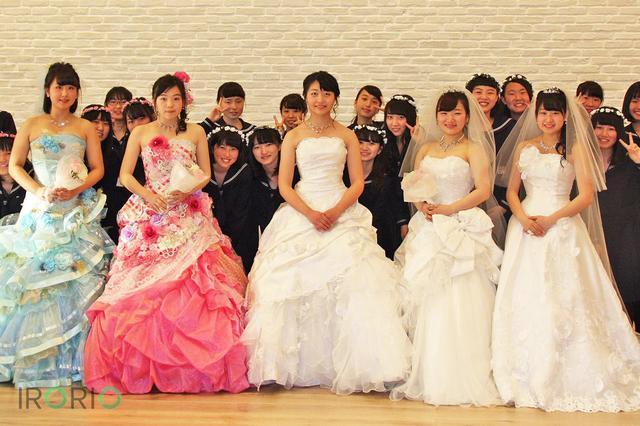 画像1: 山形市の市立商業高校の女子生徒たちが4月30日、市内のブライダル会場で同じ女子高校生向けの結婚式体験フェアを開催し、話題になっています。 同校に背景を取材しました。 市内の高校生の9割に結婚願望 フェアは、同校のクラブ活動・産業調査部が昨年度から取り組む「人口増大計画」の一環です。 「人を増やす」ことが柱のひとつで、低い状態が続く山形県内の婚姻率を上げることで子供が増えると仮説を立てました。 昨年9月、ウエディングドレスを試着する機会があった部員たちは、それまで意識していなかった「結婚したい」という思いが芽生えたといいます。 さらに、調査の結果、市内の高校生700人のうち90パーセントが結婚願望を持つ事実も判明しました。 とても単純 [...] irorio.jp