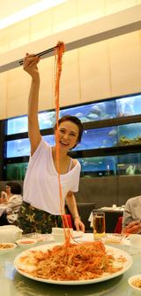 """画像: 旧正月のメインフード、シンガポール版""""刺身サラダ"""" 「魚生(イューシェン)」がサービスされました。 通称「ローヘイ」と呼ばれ親しまれているそうですが・・・ 食べる前の動作がポイント。 盛られた具材を箸で高く持ち上げ、 振り上げた位置から一斉に落とします! 箸を動かす時は「ローヘイ(撈起)」と 大きな声で何度も叫びます。 これは広東語で漁師が網を引き揚げる時の動作のことで、 魚を売ることでお金が入ってくることから「お金を稼ぐ」「金持ち」というような意味合いがあるそうです。 きれいに盛られた料理がグチャグチャ・・・と、思いきや、 これが正解です。高く上げれば上げるほど縁起が良く、 具材が皿からはみ出すほどでも、「溢れるほどの大漁=豊富な金」とされているので問題なし。 料理はすべて食べないで少し残して下さい。 全部食べてしまうとお金が無くなってしまいます。"""