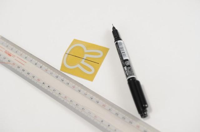 画像: ②ステッカーにガイドラインを作る 今回は、左右センター合わせが重要なので、 幅を採寸して、貼り付け用透明シートの上から中央にラインを引く。