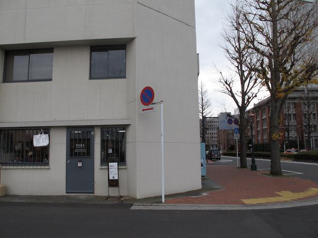 画像: 右奥に見えるのは横浜第2合同庁舎。左のドアはお店。 川沿いっていうか、海沿いっていうか、そんな場所です。