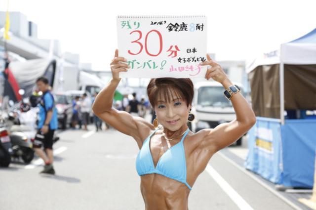画像: 女子ボディビルダーの山田純子さん。 今日はHonda向陽会ドリームレーシングチームの応援に駆けつけたとのこと。