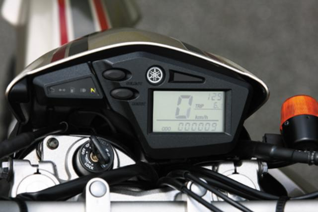 画像: フロントまわりの軽量化にも寄与する小型スピードメーターは時計、ツイントリップ機能付き。グリーンのバックライトで視認性も高い。
