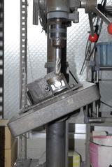 画像: ピストンヘッドのバルブの「逃げ」をボール盤で切削加工するための治具。垂直にバイト(歯)が当たるように、溶接作業のワンオフでつくられた。削りすぎれば当然ながらピストンヘッドに穴が開く。ちなみにこのピストンは、GSX400Eのものではなく参考品だ。