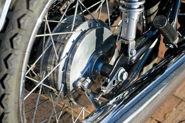 画像: 有効径180㎜のドラム式ブレーキをリア側に採用。消音器は3つのセパレーターを持つ厚みのある構造であり、排気音の静かさをセールスポイントにしていた。